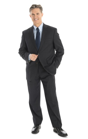 Full length portrait of confident mature businessman in formals standing isolated over white background