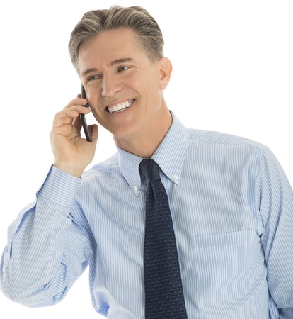 answering phone: Happy mature businessman looking away while answering smart phone against white background