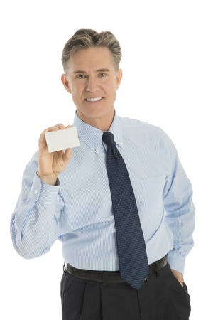 Portrait of confident mature businessman showing blank business card against white background