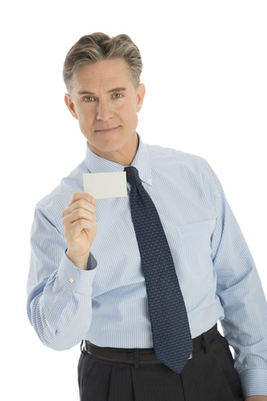 Portrait of handsome mature businessman holding blank business card against white background photo