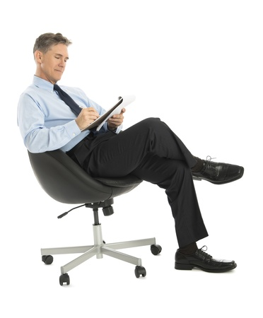 Mature businessman writing in note pad while sitting on office chair against white background photo