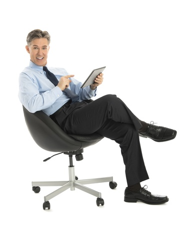 Portrait of happy mature businessman pointing at digital tablet while sitting on office chair against white background photo