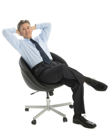 people from behind: Portrait of relaxed mature businessman with hands behind head sitting on office chair against white background