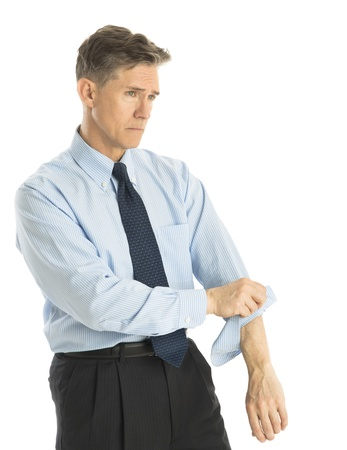 Exhausted mature businessman rolling up his sleeves while standing isolated over white background photo