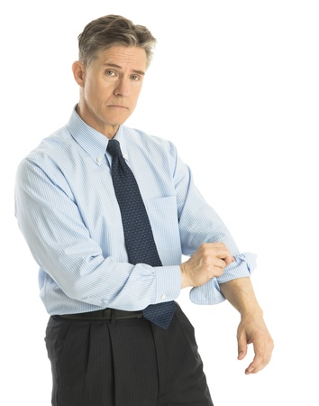 Portrait of tired mature businessman rolling up his sleeves while standing isolated over white background photo