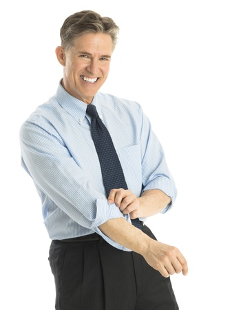 rolled up sleeves: Portrait of happy mature businessman rolling up his sleeves while standing against white background
