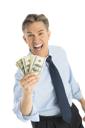 Portrait of cheerful mature businessman holding dollar bills while standing against white background photo