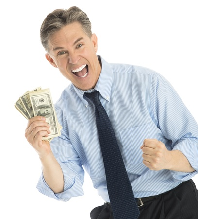 Portrait of successful mature businessman showing one hundred dollar bills while standing against white background photo