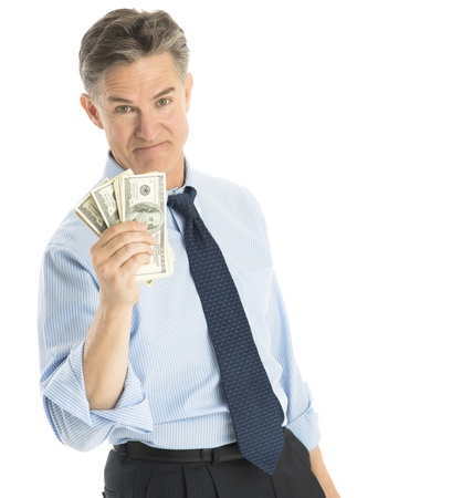 Portrait of confident mature businessman showing one hundred dollar bills against white background photo