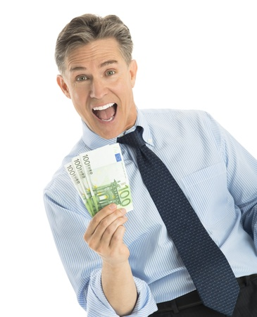 Portrait of excited mature businessman showing euro banknotes while standing against white background photo