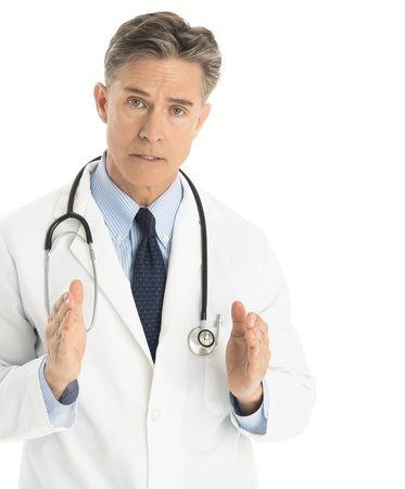 Portrait of serious male doctor gesturing against white background photo