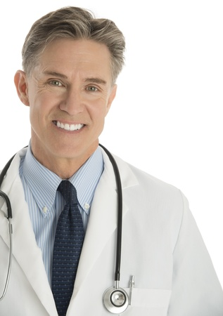 Close-up portrait of happy male doctor standing against white background photo