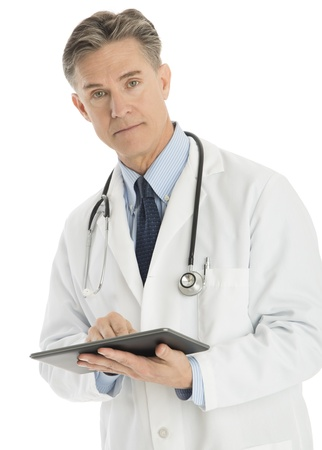 Portrait of confident male doctor holding digital tablet while standing against white background photo