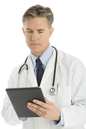 Confident mature male doctor using digital tablet isolated over white background photo