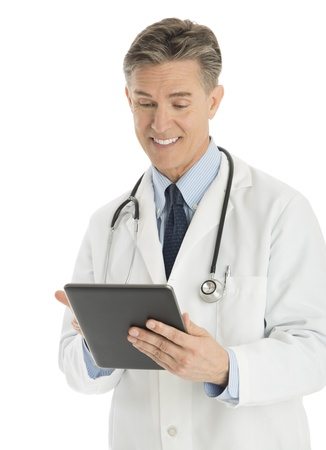Happy mature male doctor using digital tablet against white background photo