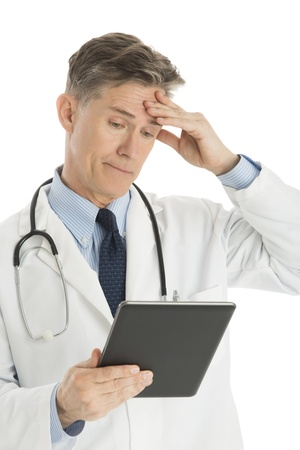 Confused mature male doctor looking at digital tablet isolated over white background