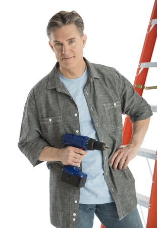 Portrait of confident male carpenter holding drill while standing against white background photo
