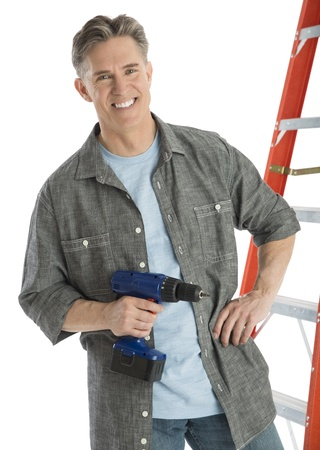 Portrait of happy male carpenter holding drill while standing against white background photo