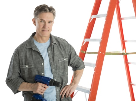 Portrait of confident male carpenter holding drill while standing by ladder against white background