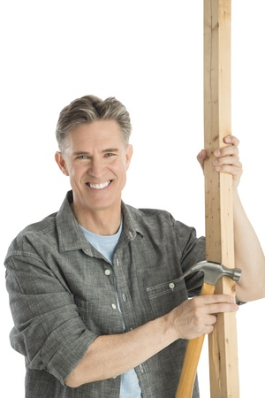 Portrait of happy male carpenter holding hammer and wooden plank against white background Standard-Bild