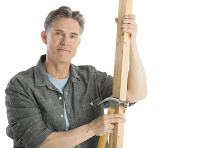 fully unbuttoned: Portrait of confident male carpenter holding hammer and wooden plank against white background