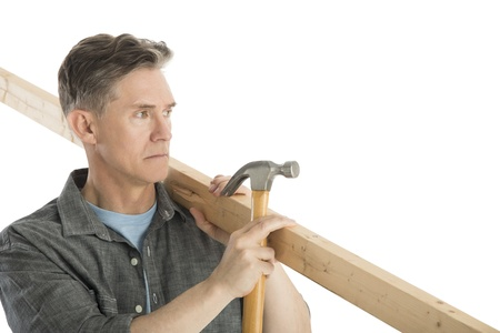 fully unbuttoned: Male carpenter looking away while holding hammer and wooden plank against white background