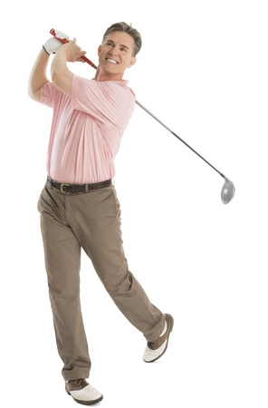 Full length of happy male golfer looking away while swinging golf club isolated on white background