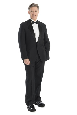 Full length portrait of mature man wearing tuxedo smiling while standing against white background