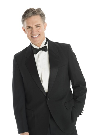 man in tuxedo: Portrait of happy mature man in tuxedo standing against white background