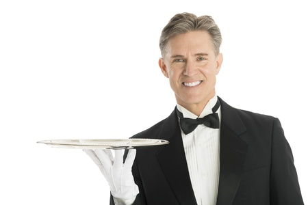 Portrait of happy waiter in tuxedo with serving tray isolated over white background photo