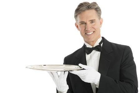 Portrait of confident waiter in tuxedo holding serving tray against white background