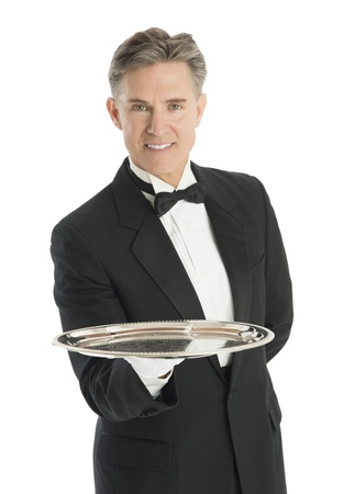 domestic staff: Portrait of confident mature waiter in tuxedo carrying serving tray against white background Stock Photo
