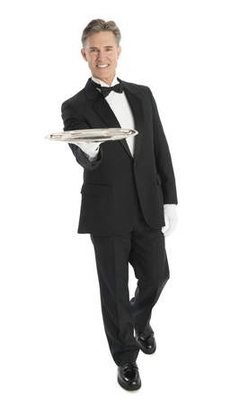 Full length portrait of happy mature waiter with serving tray walking against white background photo