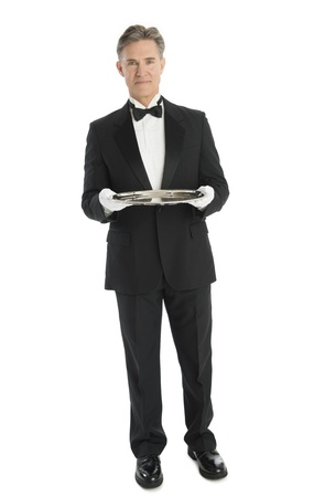 serving tray: Full length portrait of confident mature waiter with serving tray standing against white background