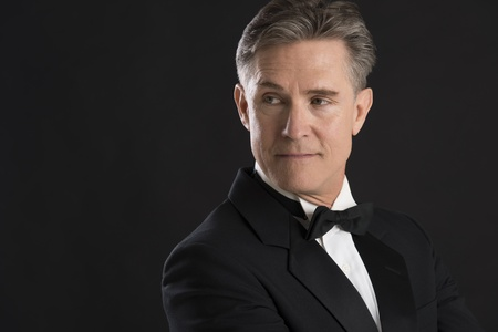 man in tuxedo: Confident mature man in tuxedo looking away against black background