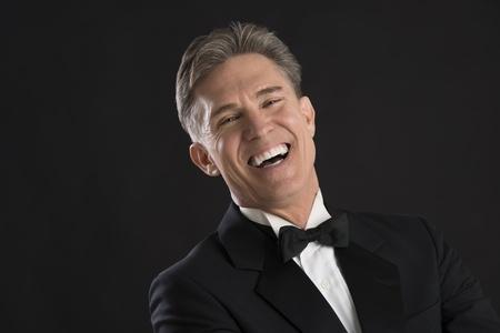 tie tuxedo: Portrait of cheerful mature man in tuxedo laughing against black background