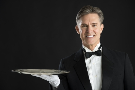 serving tray: Portrait of confident waiter in tuxedo with serving tray isolated over black background