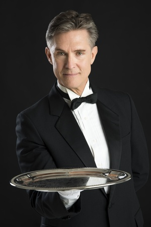 serving tray: Portrait of confident waiter in tuxedo carrying serving tray isolated on black background Stock Photo