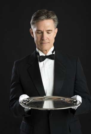 Mature waiter in tuxedo looking at serving tray isolated over black background photo