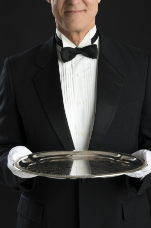 waiter tray: Midsection of mature waiter holding serving tray isolated over black background