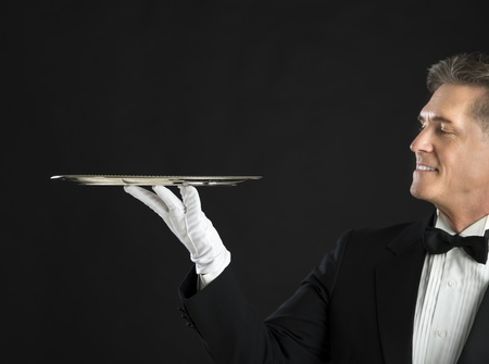 serving tray: Mature waiter smiling while looking at serving tray against black background