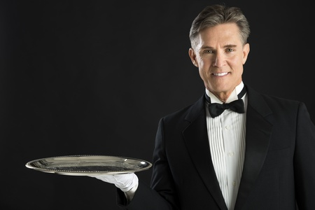 Portrait of confident waiter carrying serving tray isolated over black background photo