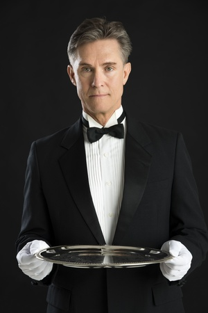 uniform attire: Portrait of confident mature waiter in tuxedo holding serving tray isolated over black background