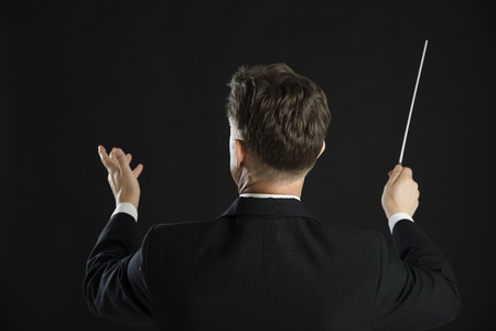 Rear view of male music conductor directing with his baton against black background Stock Photo