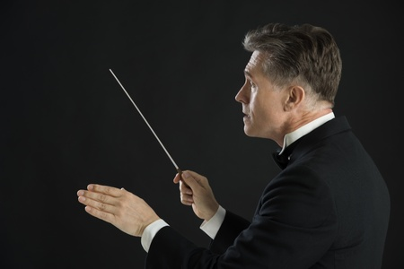 Side view of male orchestra conductor directing with his baton against black background Foto de archivo