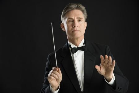 Confident mature male orchestra conductor directing with his baton against black background photo