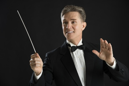 conductors: Mature male orchestra conductor looking away while directing with his baton against black background