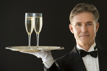 Portrait of confident mature waiter in tuxedo carrying serving tray with champagne flutes against black background photo