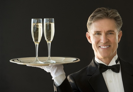domestic staff: Portrait of happy mature waiter in tuxedo carrying serving tray with champagne flutes isolated on black background