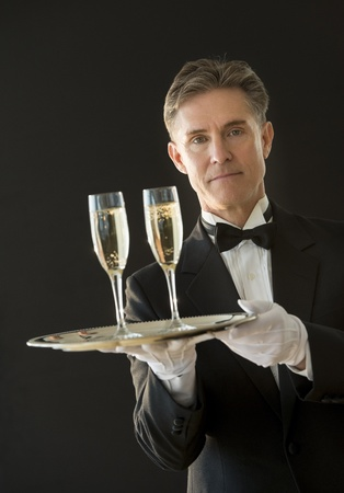 serving tray: Portrait of confident mature waiter in tuxedo holding serving tray with champagne flutes against black background